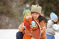 Chinese mother playing in the snow with children