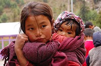 A Nepalese girl takes care of her infant sister at a pooja worship ceremony in Manang, Nepal April 23, 2007