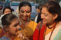 A Bangladeshi teacher feeds pitha rice cake to her student at Poush Mela 1414 Winter festival at Romna Botomul in Dhaka, The capital city of Banglades...