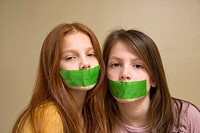 Preteen girls with green tape on their mouths