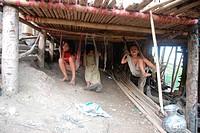 Children on swing under the hut Rangamati, Bangladesh June 2009