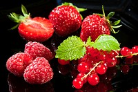 Strwaberries, raspberries and redcurrant on a black background