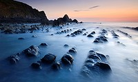 High tide gradually submerges the rocky shores of Blegberry Bay at sunset, Hartland, Devon, England, United Kingdom, Europe