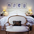 BEDROOMS: All white romantic styling, gilded Louis style sette at foot of bed, symmetric, nightstands with boudoir lamps and vases of casablanca lilie...