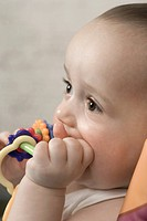 A baby gnawing on a teething ring