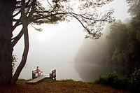 Woman having morning coffee on dock - Brevard, North Carolina