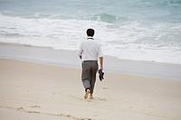 A Scandinavian man walking on the beach, Brazil.