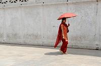 nepalese lady holding red umbrella taking a walk, kathmandu, nepal