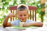 Cute little boy eating oudding outside