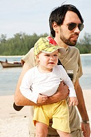 Father carrying his daughter on beach