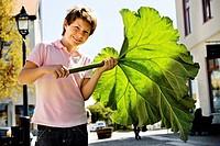 Boy holding rhubarb leaf