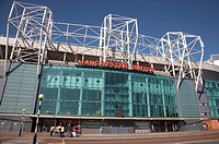 Exterior view of Manchester United football stadium with Sir Matt Busby statue, Manchester UK