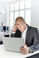 Man sitting in office looking at laptop