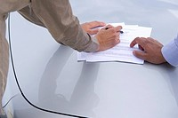 Business people looking at paperwork in parking lot