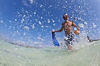 Hispanic man walking in water with snorkel gear