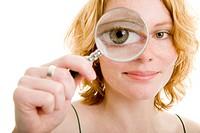 Junge Frau schaut durch eine runde Lupe
