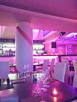 Interior of empty beautiful restaurant illuminated with purple light