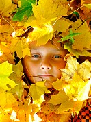 Face of child in leaves in autumn