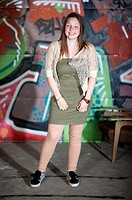 A young woman posing in front of a graffity