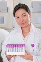 Technician holding vials in laboratory