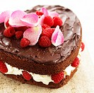 Heart_shaped chocolate cake with raspberries, cream and rose petals