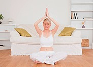 Relaxed blond_haired woman practicing yoga at home