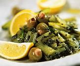 Dandelion leaf salad with olives on plate with lemon wedges