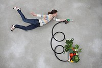 Mid adult woman holding industrial hose connected to vegetable box
