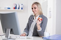 Germany, Bavaria, Munich, Businesswoman using computer and holding apple