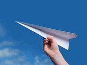 Close_up of a child´s hand holding a paper airplane