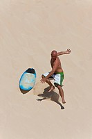 A surfer riding a dune crashes of board