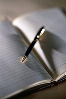 Close_up of a ballpoint pen on an open notebook