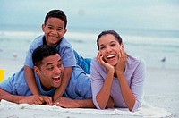Parents smiling with their son on the beach