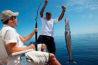 Two mid adult men fishing, Faafu Atoll, Maldives
