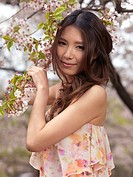 Portrait of a beautiful young smiling Asian woman standing at a blooming cherry tree in a park