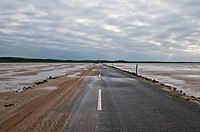 Sand covered road to Lindisfarne - Holy island at low tide, Lindisfarne, England  The road is only passable for a few hours around low tide, tidal cha...