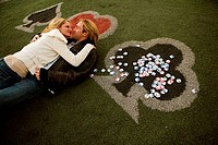High angle view of a young couple lying on grass near gambling chips