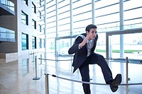 Businessman jumping over rope in lobby