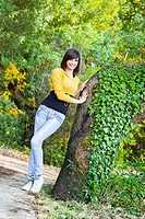 Attractive young woman is posing happy by the big tree