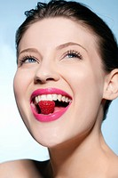 Smiling woman eating a raspberry