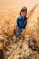 A young girl searches a harvested field for leftover stalks of wheat