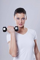 Mid adult woman with barbells against white background, smiling, portrait