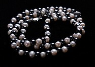White pearls and black stone beads on a thread