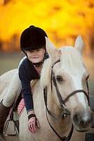 Caucasian girl riding on horse