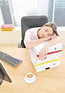 Woman sleeping in office on file folders