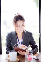 Young businesswoman holding personal organizer in cafe