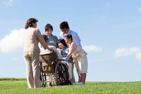 Senior man in wheelchair with his family at the park