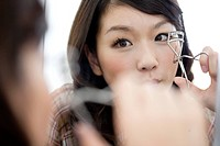Young woman using eyelash curler, close up, differential focus