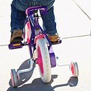 Back view of girl riding bicycle with training wheels.