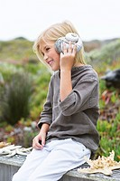 Girl listening to conch shell and smiling